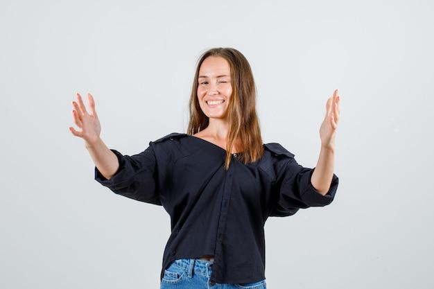 Jonge vrouw in overhemd, korte broek die handen uitstrekt en er vrolijk uitziet