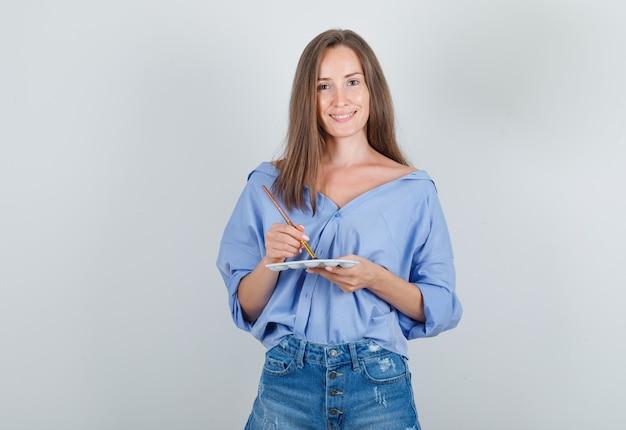 Jonge vrouw in overhemd, korte broek die verfborstel over palet houdt en vrolijk kijkt