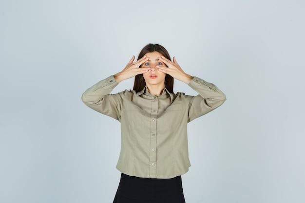 Jonge vrouw in overhemd, rok die door vingers kijkt en verbaasd kijkt