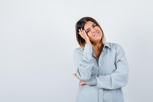 Jonge vrouw in oversized shirt die het gezicht aan de kant dempt en er gelukkig uitziet, vooraanzicht.