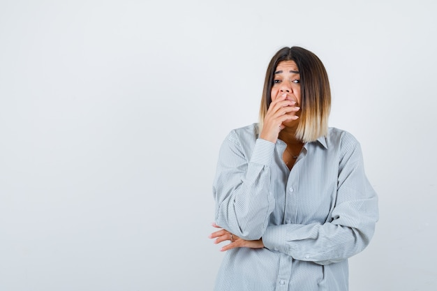 Jonge vrouw in oversized shirt hand op mond houden en perplex kijken, vooraanzicht.