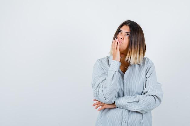 Jonge vrouw in oversized shirt met hand op kin en attent, vooraanzicht.