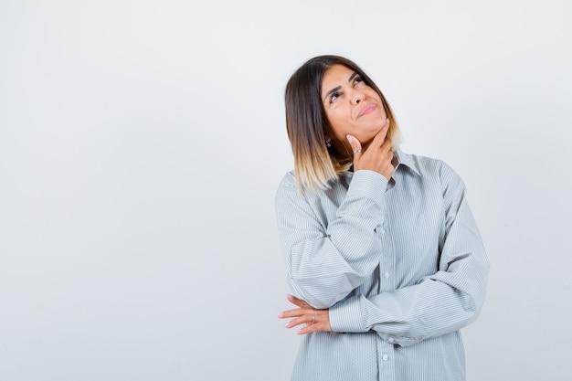 Jonge vrouw in oversized shirt staat in denkende pose en kijkt peinzend, vooraanzicht.