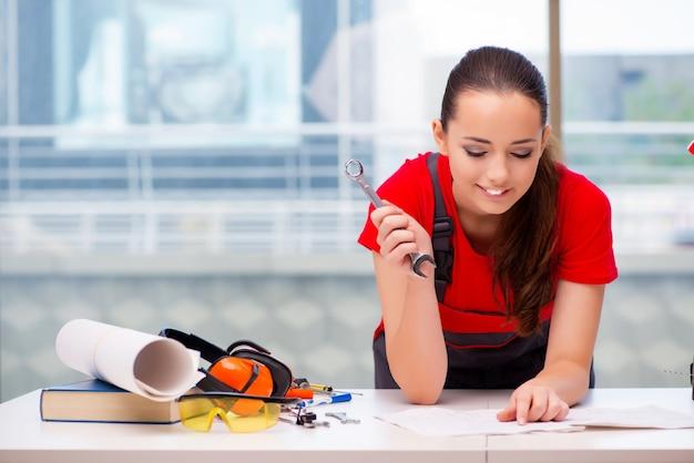 Jonge vrouw in overtrekken die reparaties doen