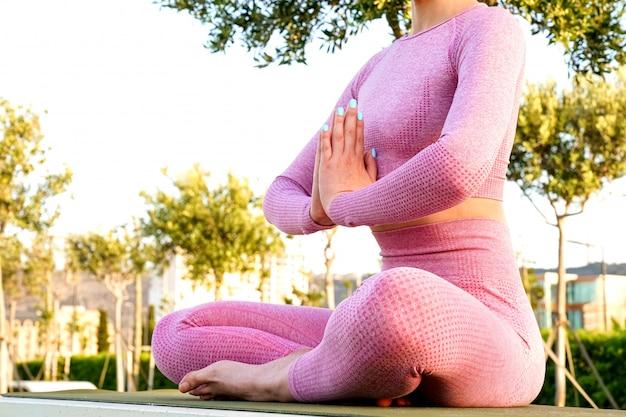Jonge vrouw in paars shirt en broek op het gras overdag in groen park mediteren en yoga doen in verschillende poses