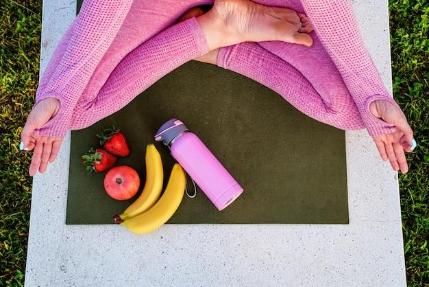 Jonge vrouw in paars shirt en broek op het gras overdag in groen park mediteren yoga fles