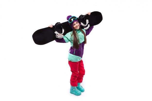 Jonge vrouw in paarse ski-outfit houd snowboard op sholders