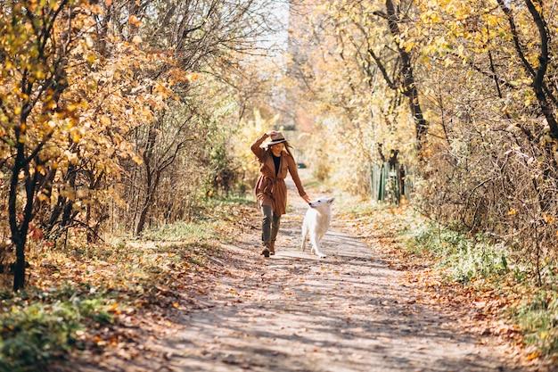 Jonge vrouw in park met haar witte hond