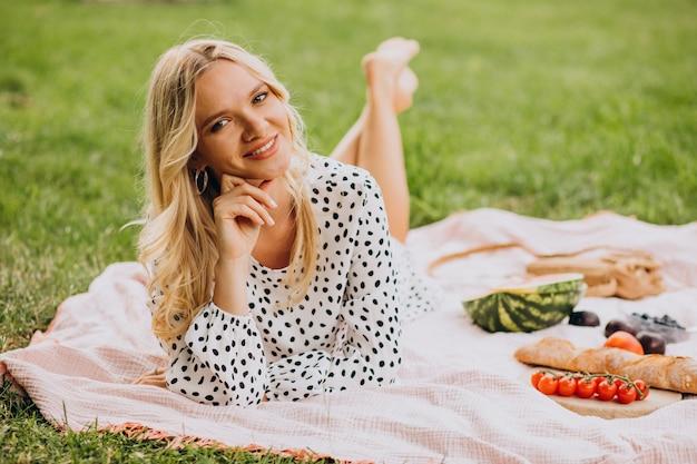 Jonge vrouw in park watermeloen eten