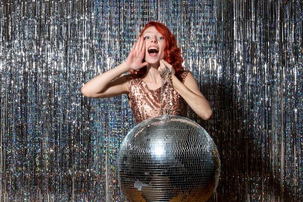 Jonge vrouw in partij met discobal op heldere gordijnen