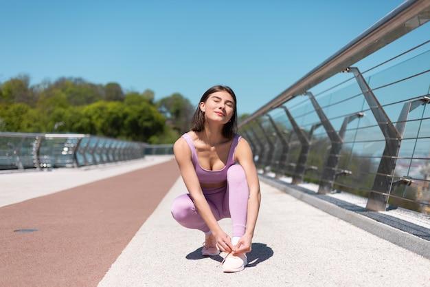 Jonge vrouw in passende sportkleding op brug bij warme zonnige ochtend banden schoenveters