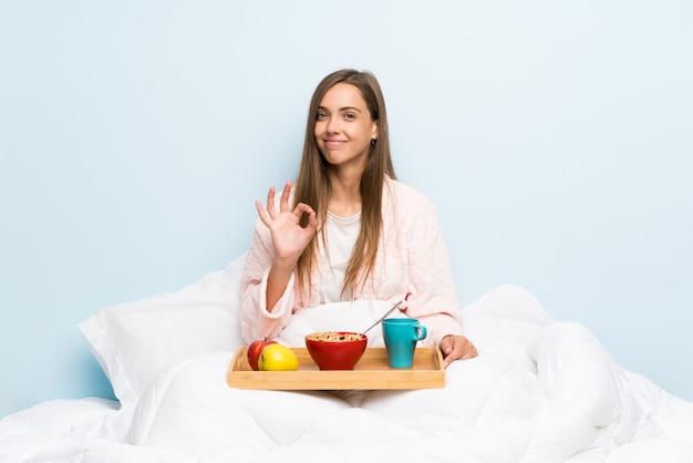 Jonge vrouw in peignoir met ontbijt die een ok teken met vingers tonen