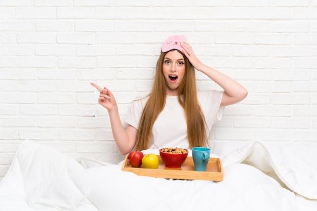 Jonge vrouw in peignoir met verrast ontbijt en het richten van vinger aan de kant