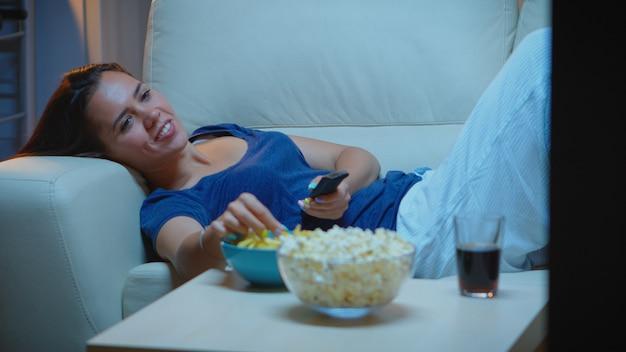 Jonge vrouw in pijamas rusten liggend op de bank voor tv glimlachen. gelukkige, geamuseerde, eenzame dame die van de avond geniet terwijl ze op een comfortabele bank zit en televisie kijkt terwijl ze popcorn en snacks eet