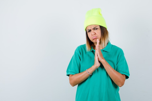 Jonge vrouw in polo t-shirt, muts met handen in biddend gebaar en boos kijken, vooraanzicht.