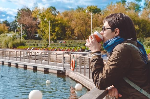 Jonge vrouw in profiel koffie drinken, staat op de pier van de stadsvijver en kijkt naar het water