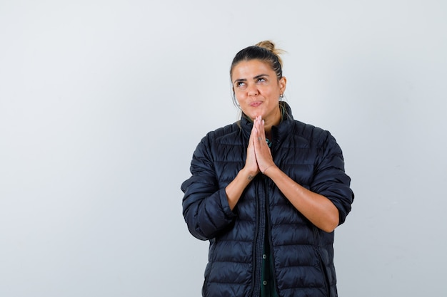 Jonge vrouw in puffer jasje met handen in biddend gebaar, opzoeken en dromerig kijken, vooraanzicht.
