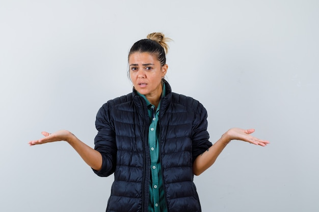 Jonge vrouw in pufferjack die hulpeloos gebaar toont en verbaasd kijkt, vooraanzicht.