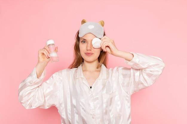 Jonge vrouw in pyjama en slaapmasker haar gezicht schoonmaken met spray op roze