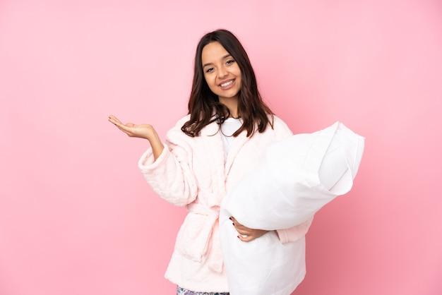 Jonge vrouw in pyjama geïsoleerd bedrijf copyspace denkbeeldig op de palm om een advertentie in te voegen