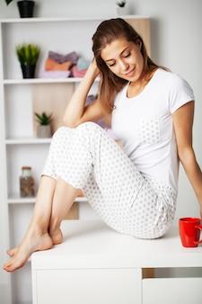 Jonge vrouw in pyjama met een mooie glimlach in de kleedkamer
