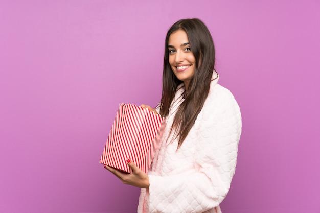 Jonge vrouw in pyjama's en peignoir over de geïsoleerde purpere popcorns van de muurholding