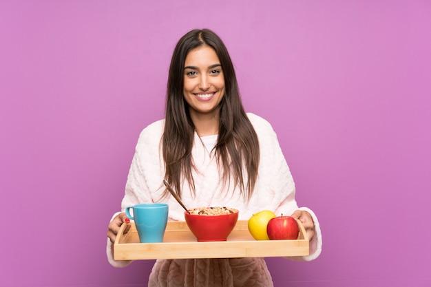 Jonge vrouw in pyjama's en peignoir over geïsoleerde purpere muur
