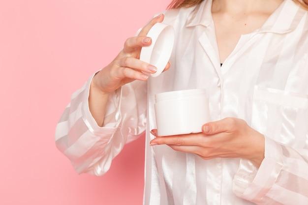 Jonge vrouw in pyjama's en slaapmasker crème op roze te openen