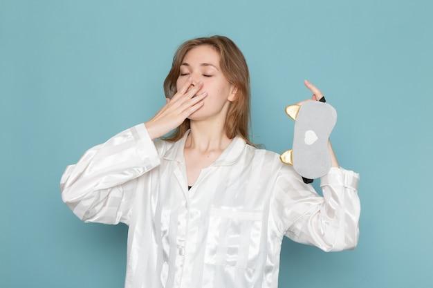 Jonge vrouw in pyjama's en slaapmasker geeuwen op blauw