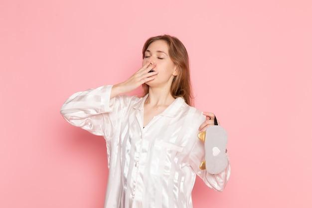 Jonge vrouw in pyjama's en slaapmasker geeuwen op roze