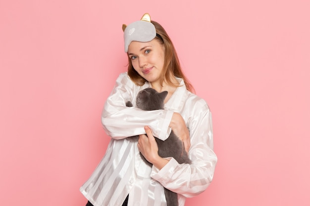 Jonge vrouw in pyjama's en slaapmasker grijs kitten op roze te houden