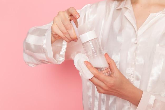 Jonge vrouw in pyjama's en slaapmasker met make-up spray op roze