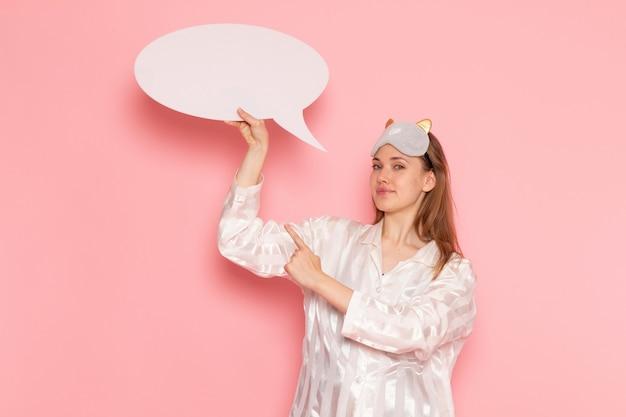 Jonge vrouw in pyjama's en slaapmasker met wit bord op roze