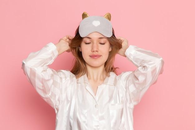 Jonge vrouw in pyjama's en slaapmasker poseren lachend op roze