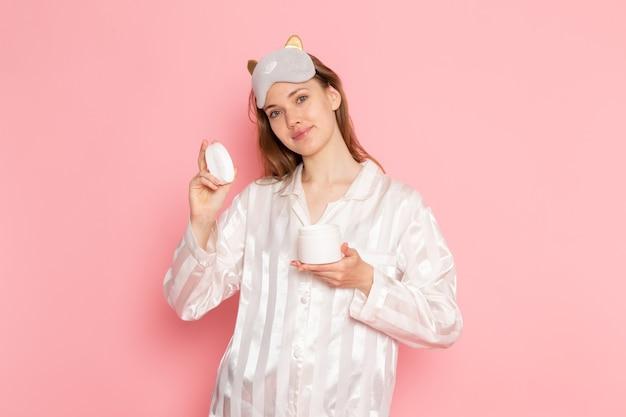 Jonge vrouw in pyjama's en slaapmasker poseren met de crème van de glimlachholding op roze