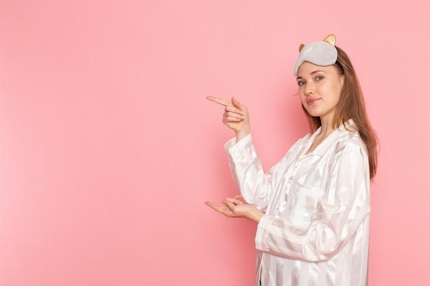 Jonge vrouw in pyjama's en slaapmasker poseren met een glimlach op roze