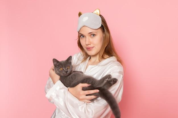 Jonge vrouw in pyjama's en slaapmasker poseren met een lichte glimlach en kat op roze