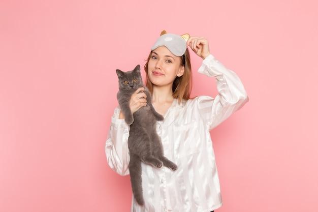 Jonge vrouw in pyjama's en slaapmasker poseren met glimlach en schattig grijs katje op roze