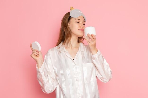 Jonge vrouw in pyjama's en slaapmasker ruikende crème op roze