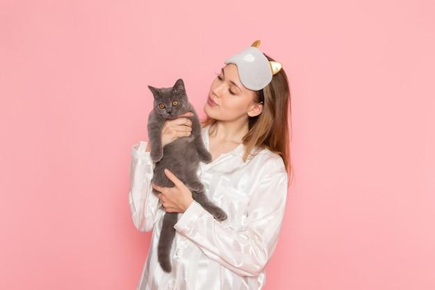 Jonge vrouw in pyjama's en slaapmasker schattige kat op roze te houden