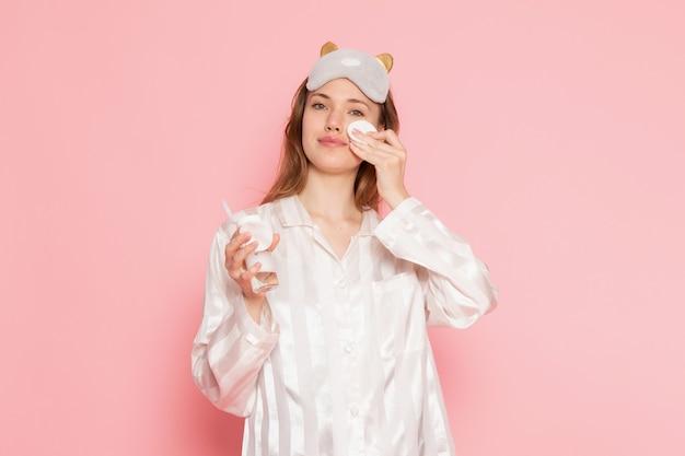 Jonge vrouw in pyjama's en slaapmasker schoonmaken van haar gezicht op roze