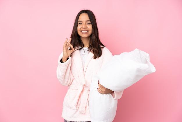 Jonge vrouw in pyjama's op roze muur die een ok teken met vingers tonen