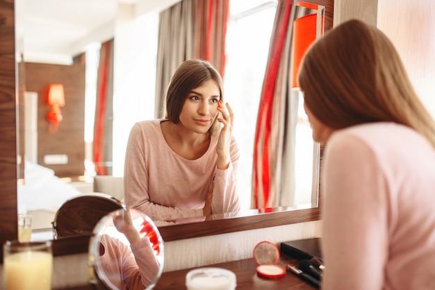 Jonge vrouw in pyjama voor de spiegel in de slaapkamer.