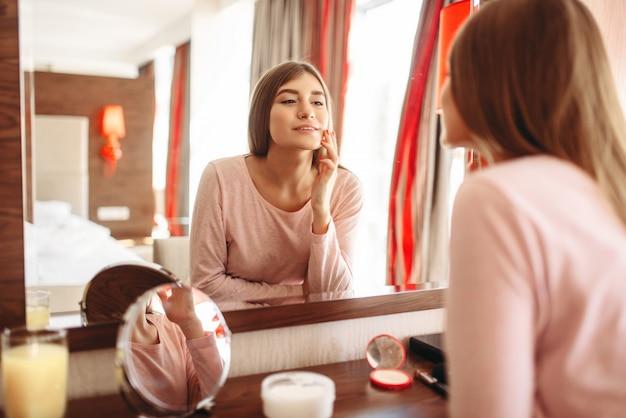 Jonge vrouw in pyjama voor de spiegel