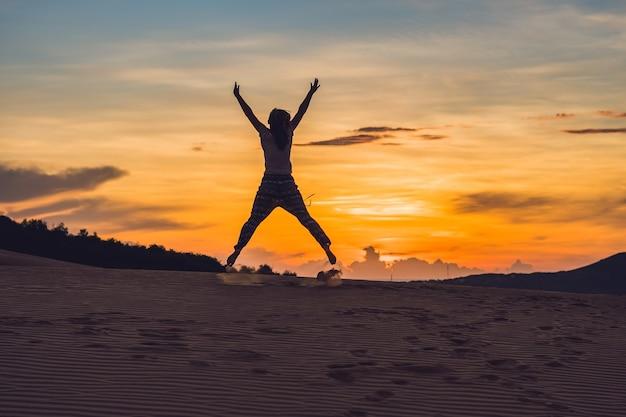 Jonge vrouw in rad zandwoestijn bij zonsondergang of dageraad