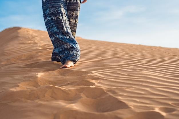 Jonge vrouw in rad zandwoestijn bij zonsondergang