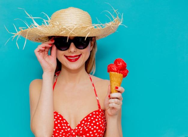 Jonge vrouw in rode bikini en strooien hoed met ijs