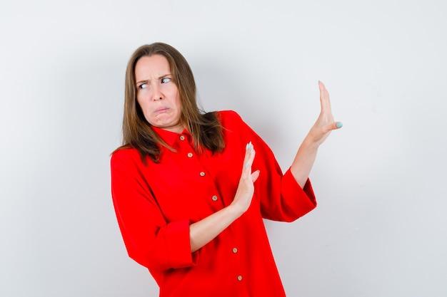 Jonge vrouw in rode blouse die een stopgebaar toont en er walgelijk uitziet, vooraanzicht.
