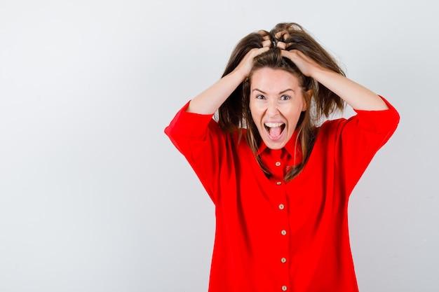 Jonge vrouw in rode blouse die haren met handen vasthoudt en er grappig uitziet, vooraanzicht.