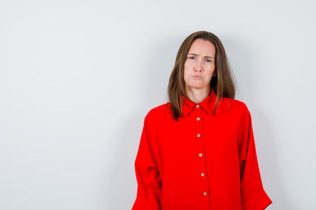 Jonge vrouw in rode blouse met een fronsend gezicht, gebogen onderlip en somber, vooraanzicht.